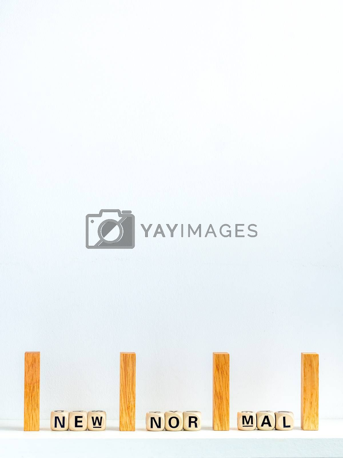 Social Distancing concept. Row of wooden dominoes with distance space and New Normal, words on wooden alphabet cube on white background with copy space, vertical style.