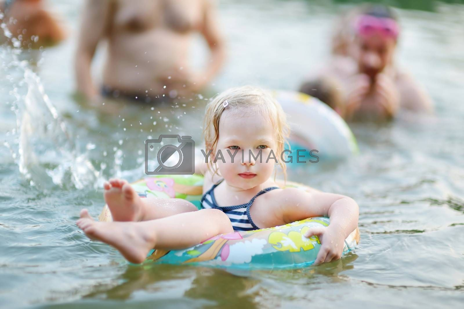 Pretty little toddler girl swimming in a lake