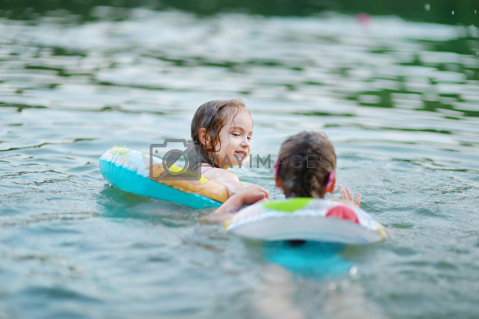 Little sisters having fun swimming in a lake at summer