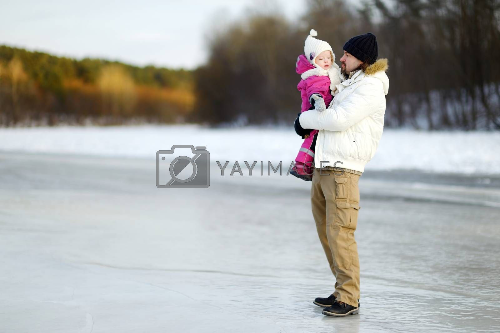 Young father and his toddler daughter on beautiful winter day