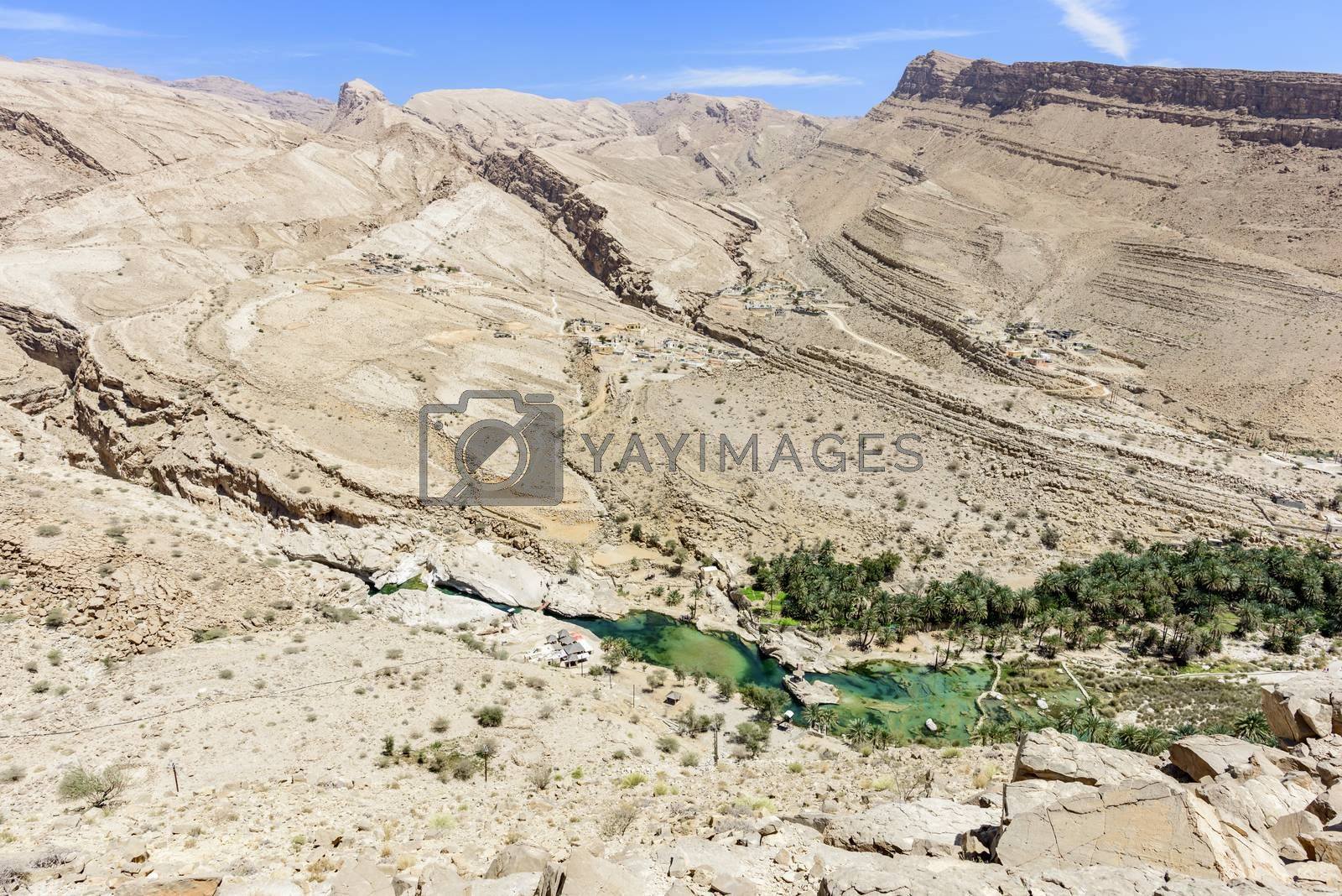 Scenic view of Wadi Bani Khalid, Sultanate of Oman. We can see the main pool and many tourists going and coming in/from the canyon. This is one of the most visited wadi in Oman with easy access. Many travel agencies are stopping by. It is a main destination.