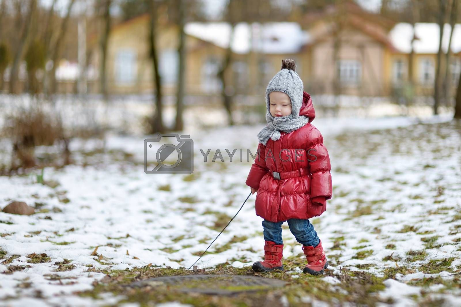 Adorable little girl having fun on beautiful winter day