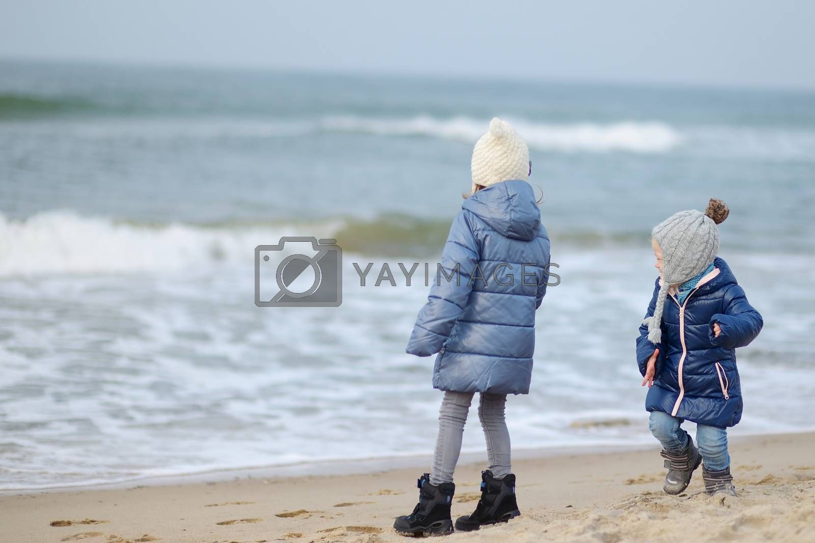 Adorable little girls playing by the ocean by maximkabb
