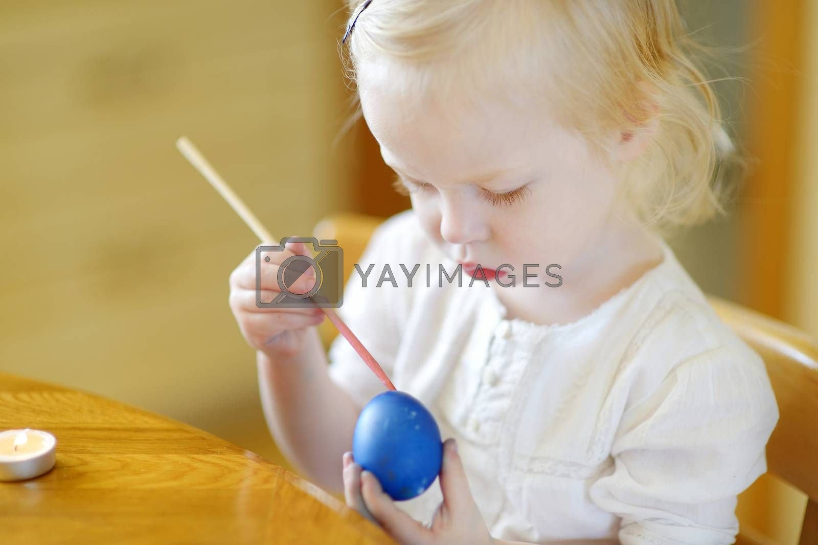 Adorable little girl coloring an Easter egg using wax and dyes