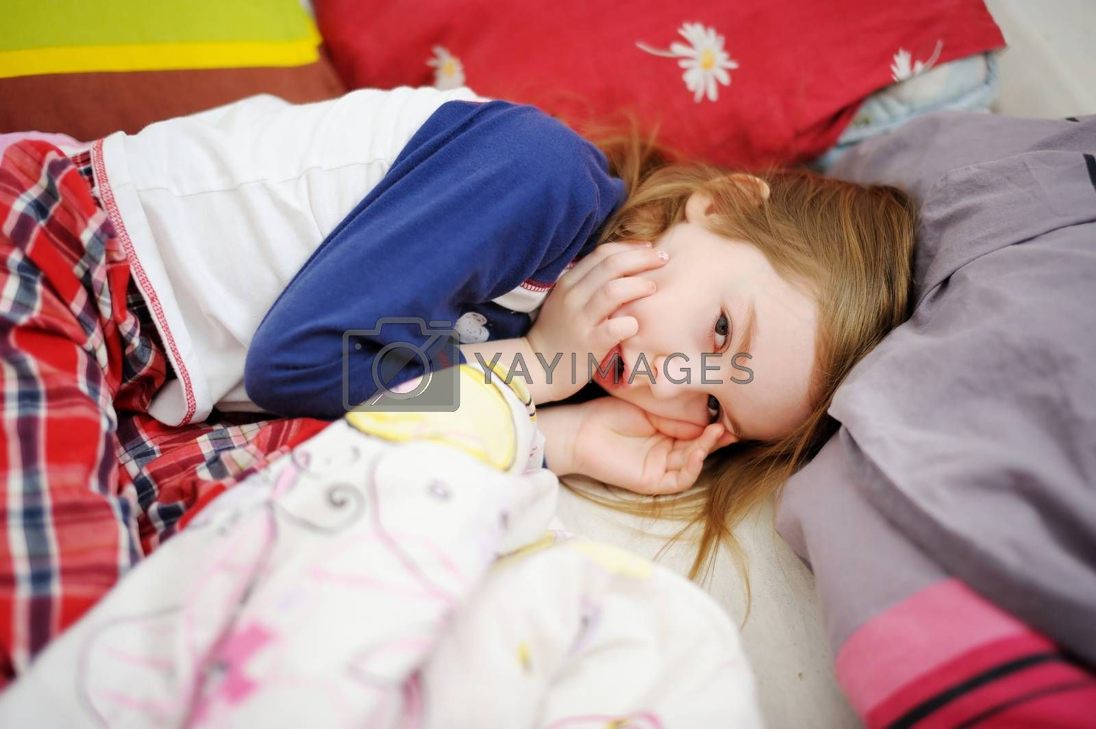 Little preschooler girl in bed on sunny morning
