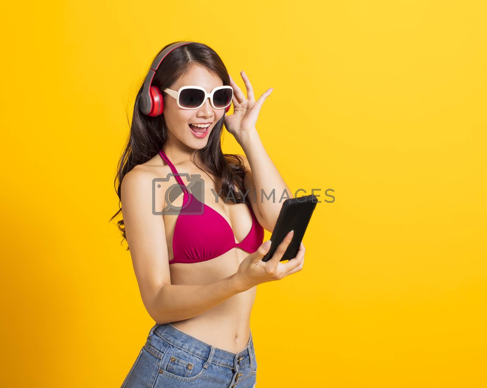 beautiful young woman wearing swimsuit bikini and watching smart phone