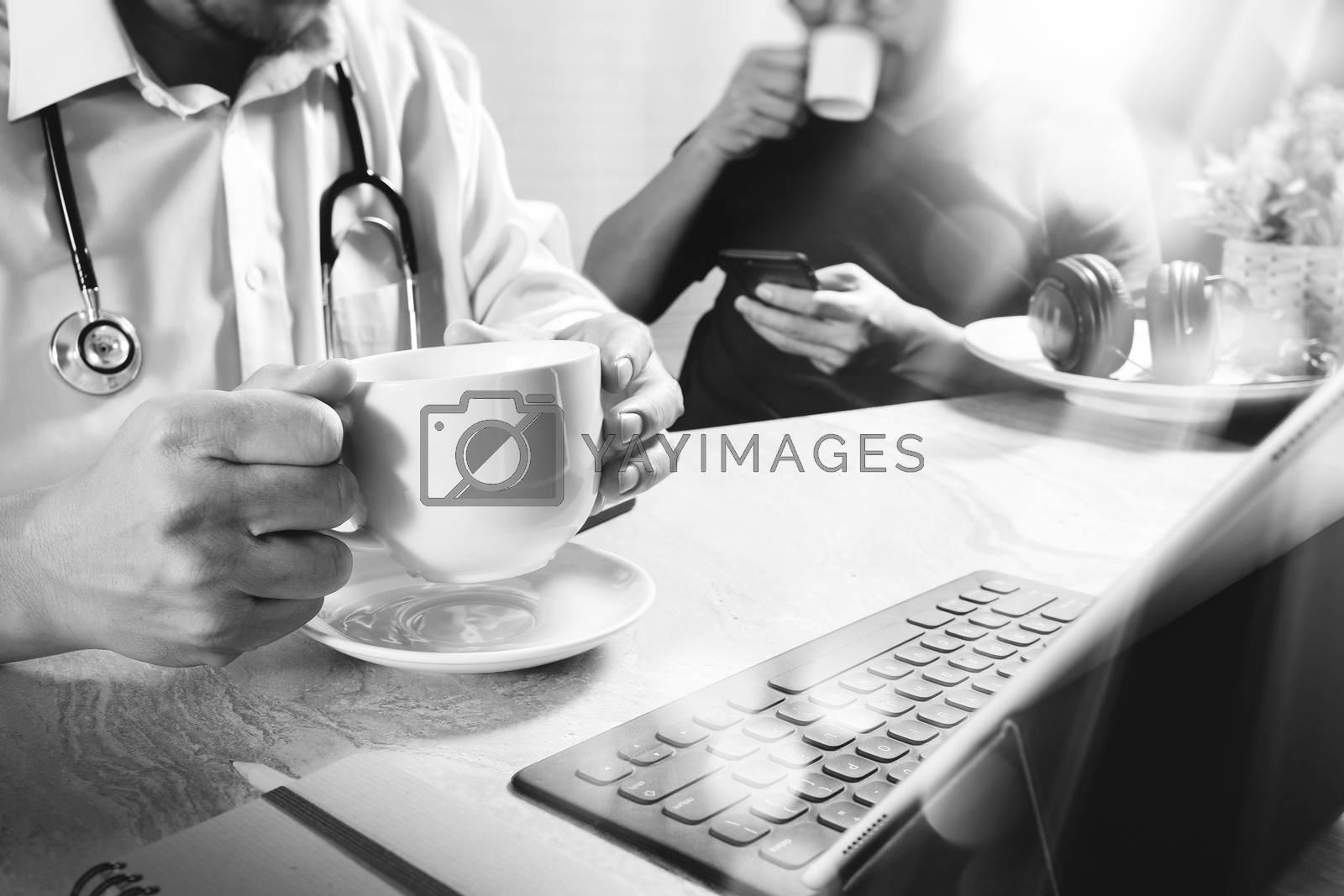 Medical doctor team taking coffee break.using digital tablet docking smart keyboard and smart phone on marble desk.listen music,filter film effect,black white