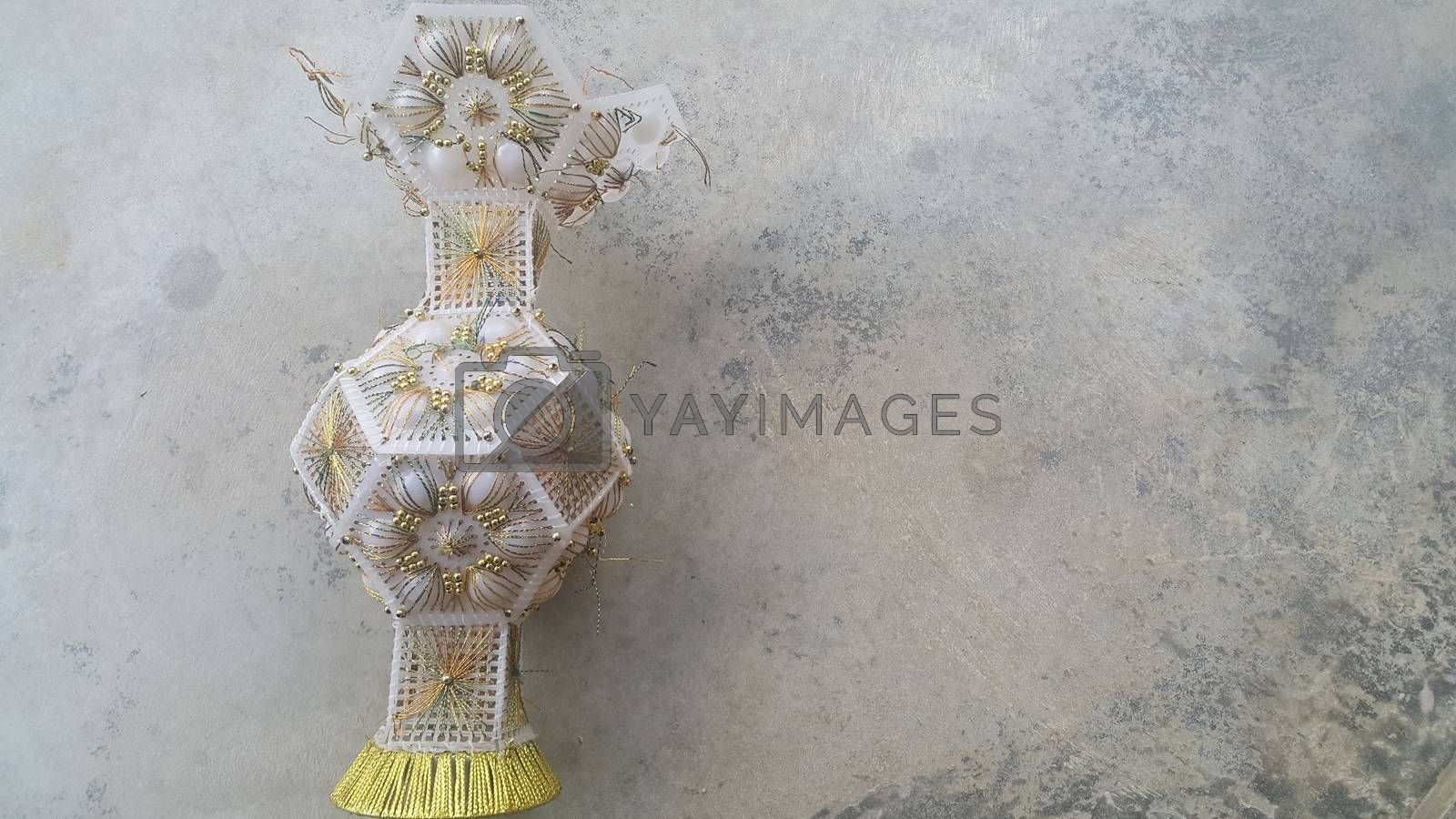A beautiful ceramic vase placed on a grey floor. The ceramic vase has lovely designs and is used for flowers or bouquet
