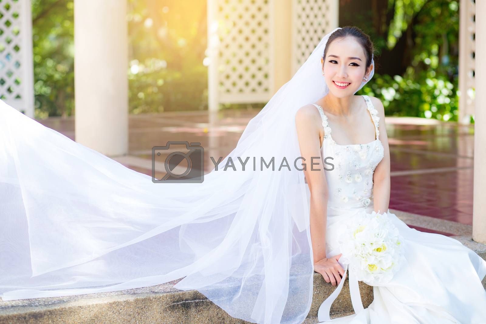bride is sitting with flowers. Beautiful Young woman posing in park or garden in white bridal dress outdoors on a bright sunny day.
