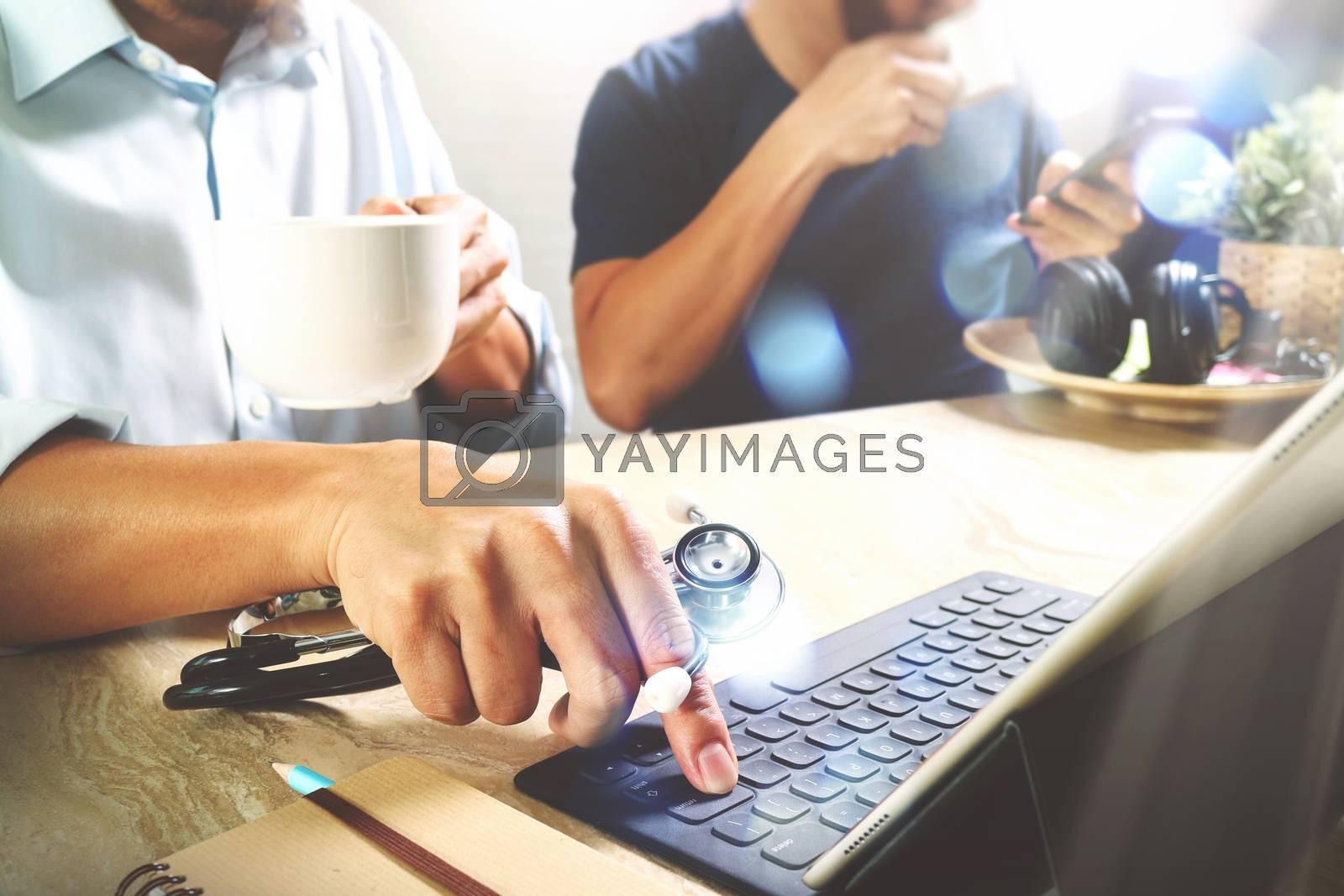 Medical doctor team taking coffee break.using digital tablet docking smart keyboard and smart phone on marble desk.listen music,filter film effect
