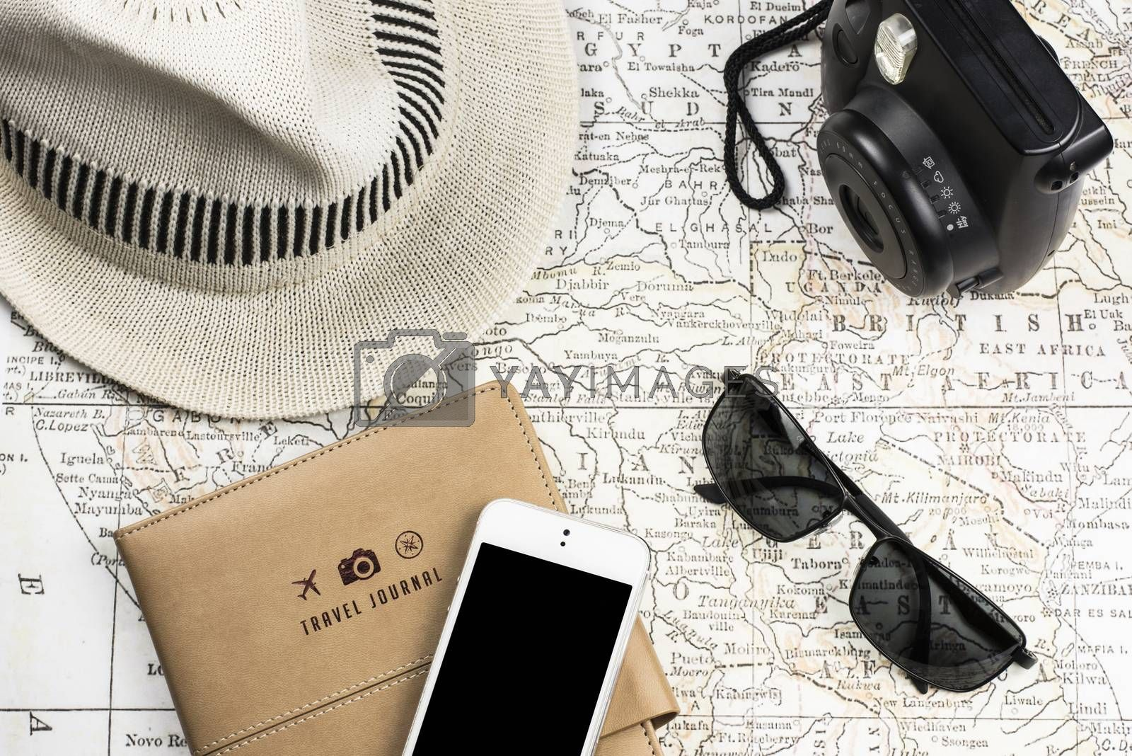 Photography of an ancient Map with a instant Camera like Polaroid, mobile phone (with black screen) sunglasses and white hat