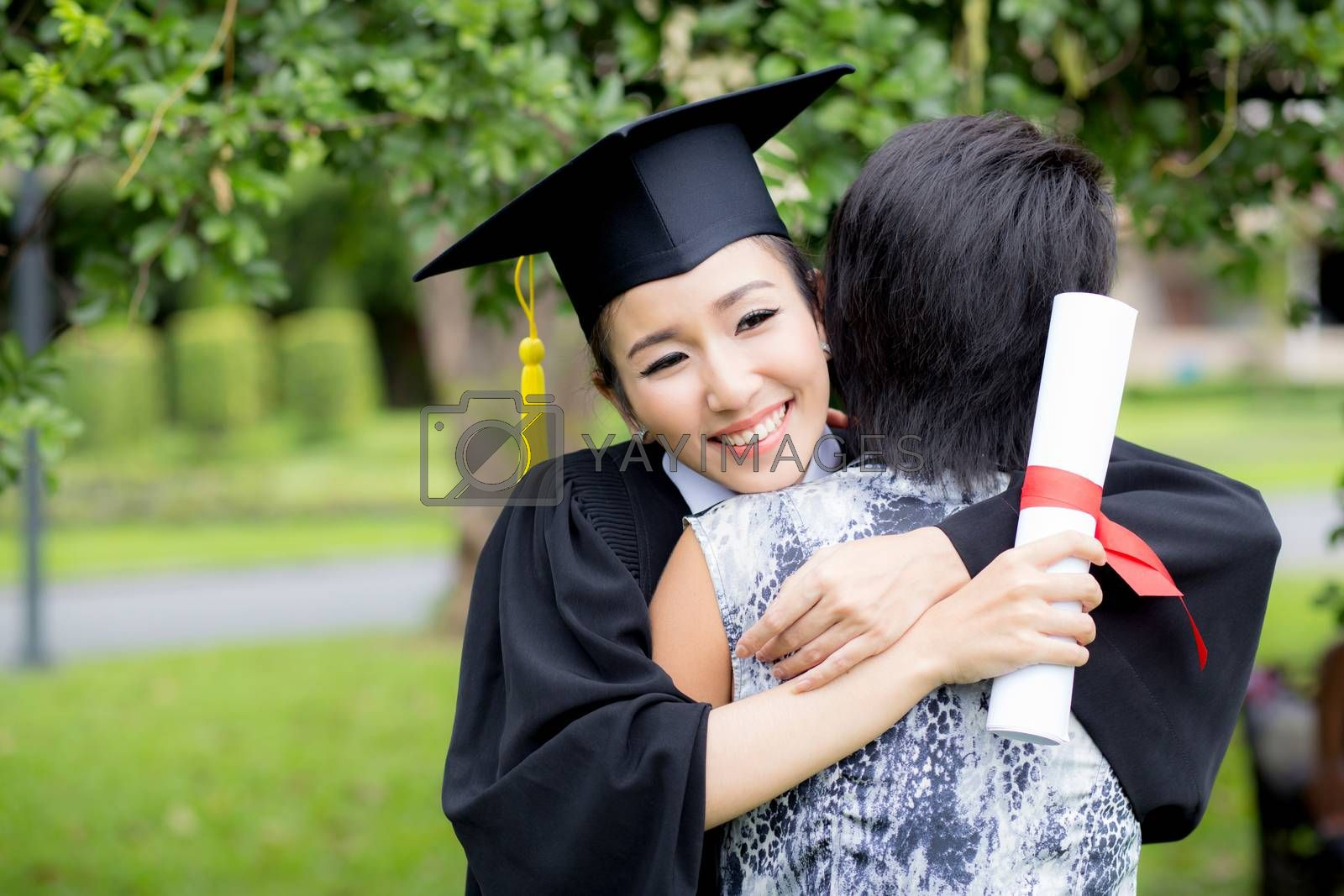 young female graduate hugging her friend at graduation ceremony