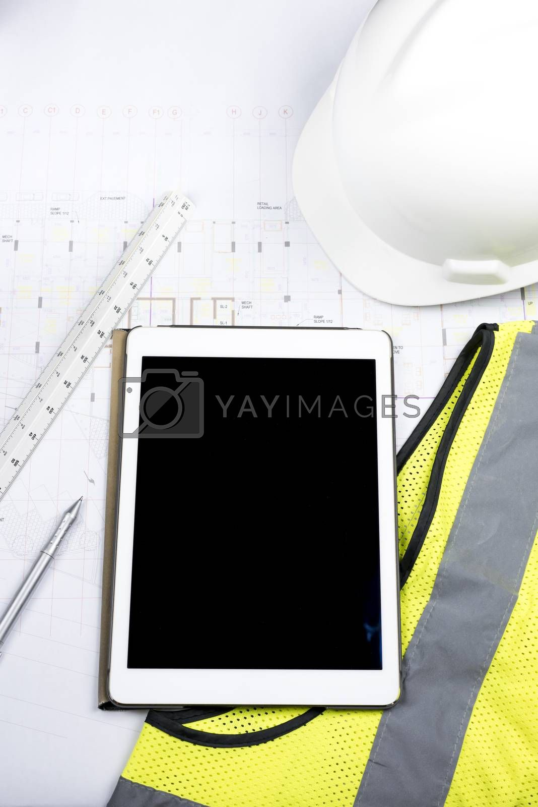 Digital tablet with black screen, hard copy of drawing, triangular scale ruler and work Personal Protective equipment (safety yellow fluorescent gilet and white helmet)