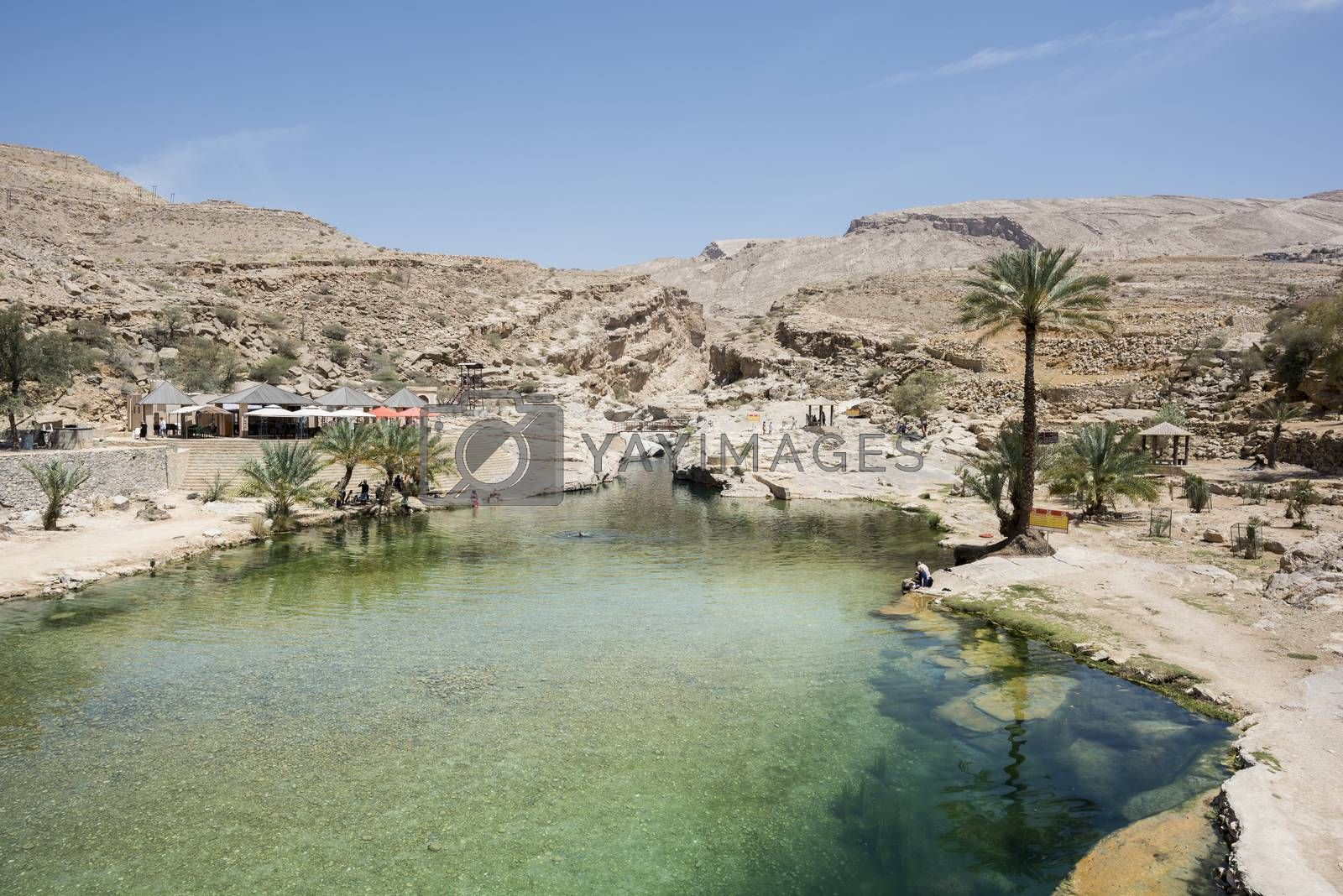 Tourists around Main pool of Wadi Bani Khalid with some going and coming back from the canyon where you can go to see the cave, Oman