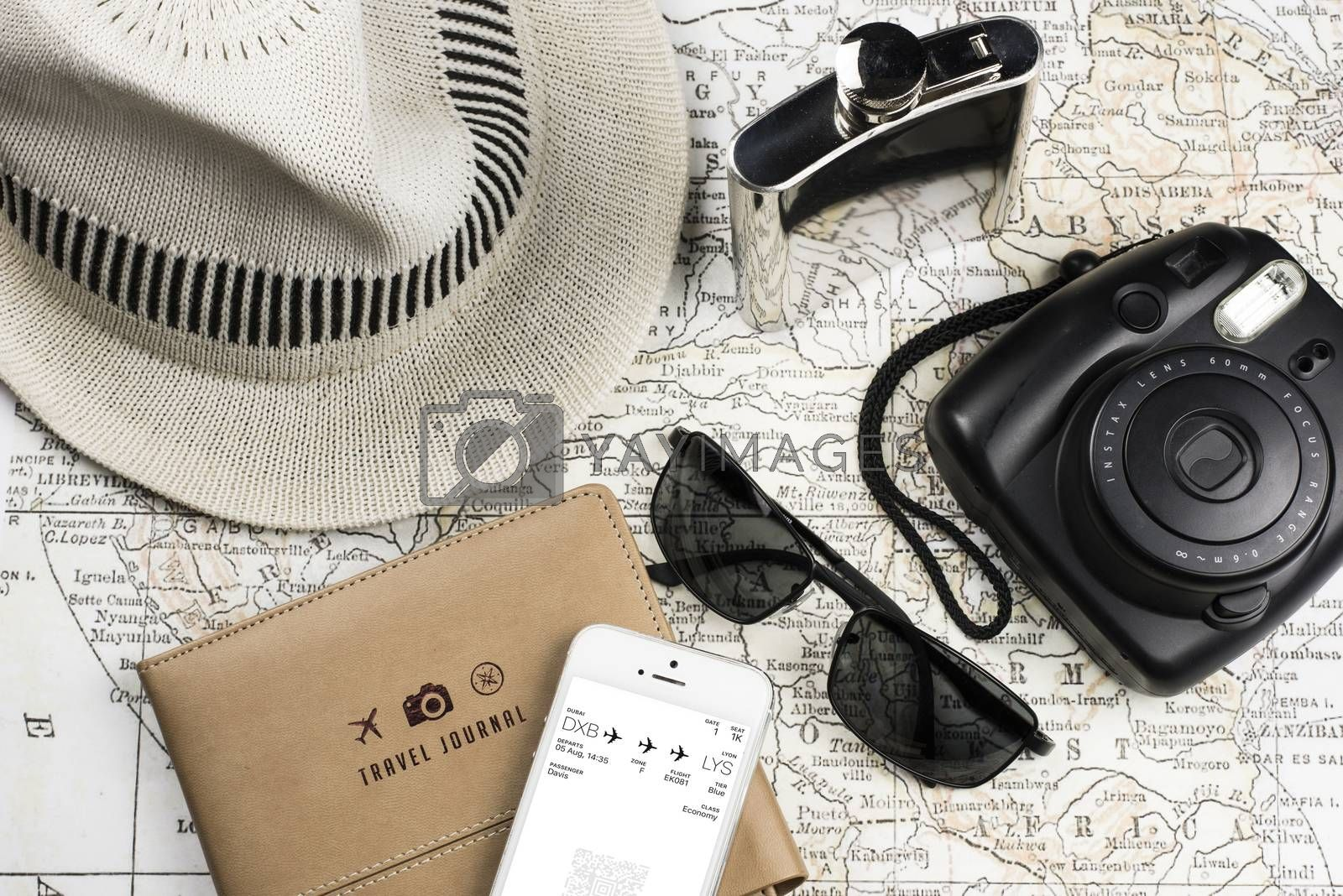Photography of an ancient Map with a instant Camera like Polaroid, mobile phone (electronic boarding pass) sunglasses, flask in stainless steel and white hat