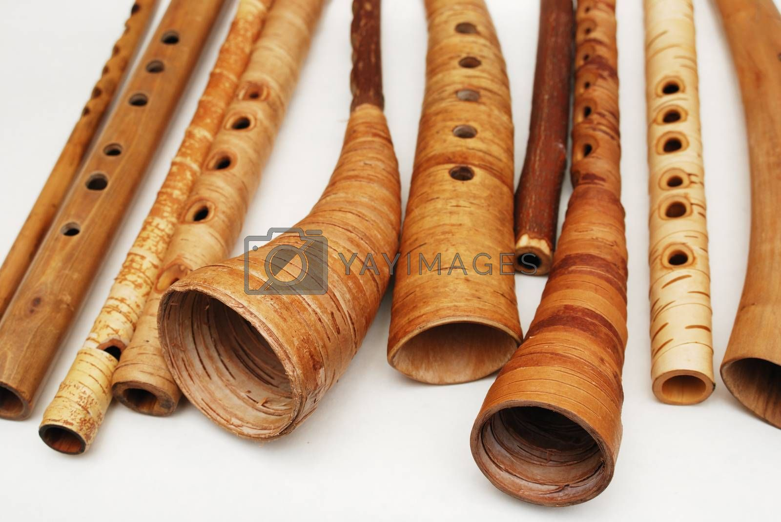 ancient woodwind folk instruments on a white