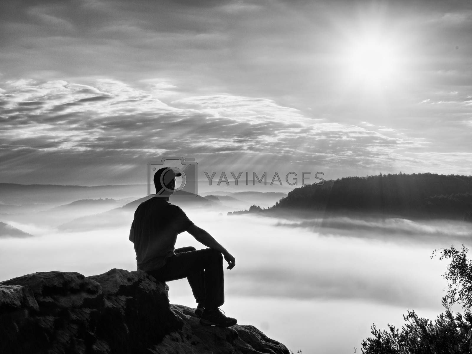 Alone hiker in black trousers and red shirt  and red cap sit on cliff's edge and looking to dreamy mist bellow. Hilly landscape with marvelous valley