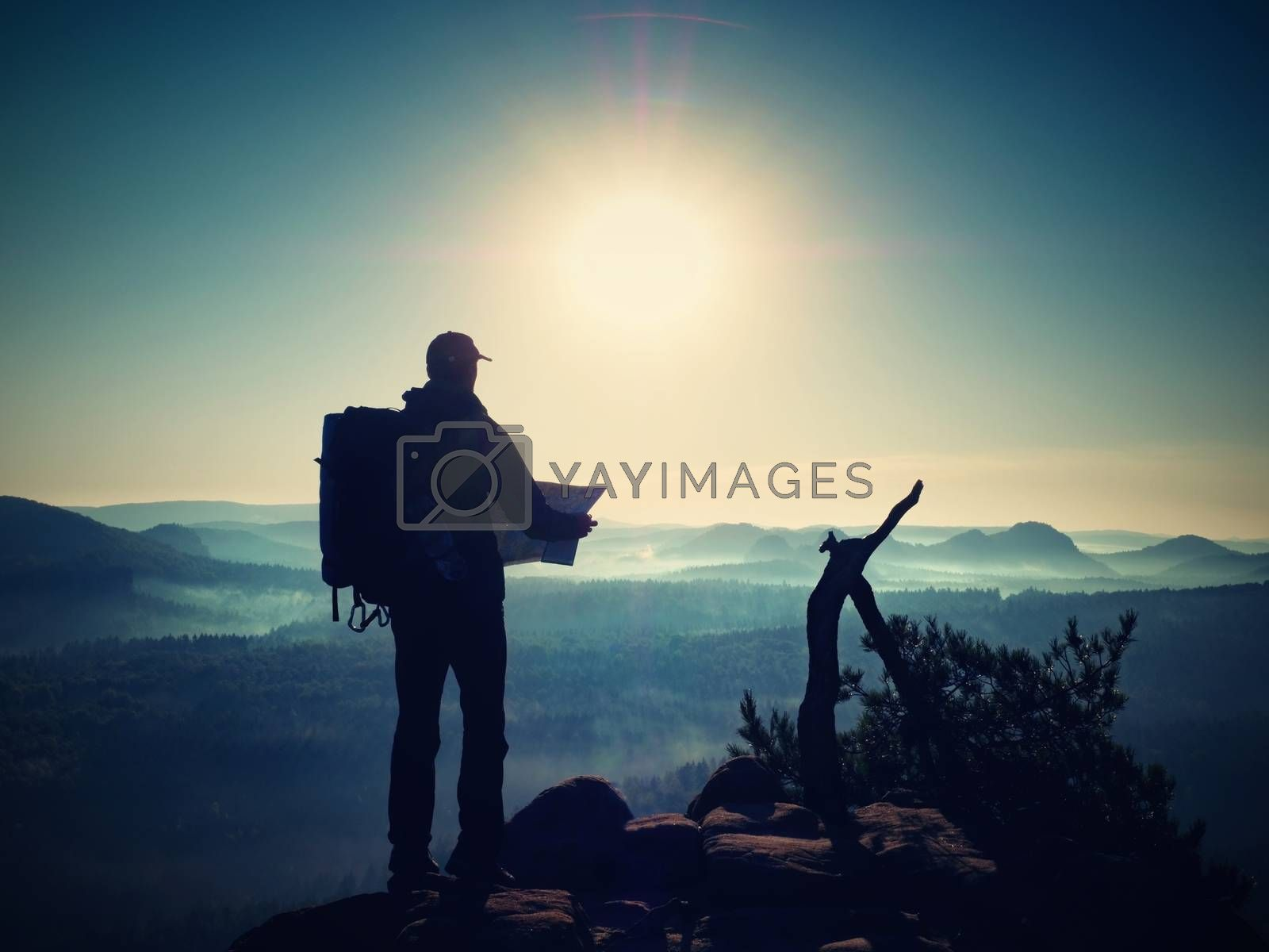 Silhouette of young tourist guide looking in paper  map in nature while hiking.  Man hiker with heavy backpack. Vintage Style Toned effect