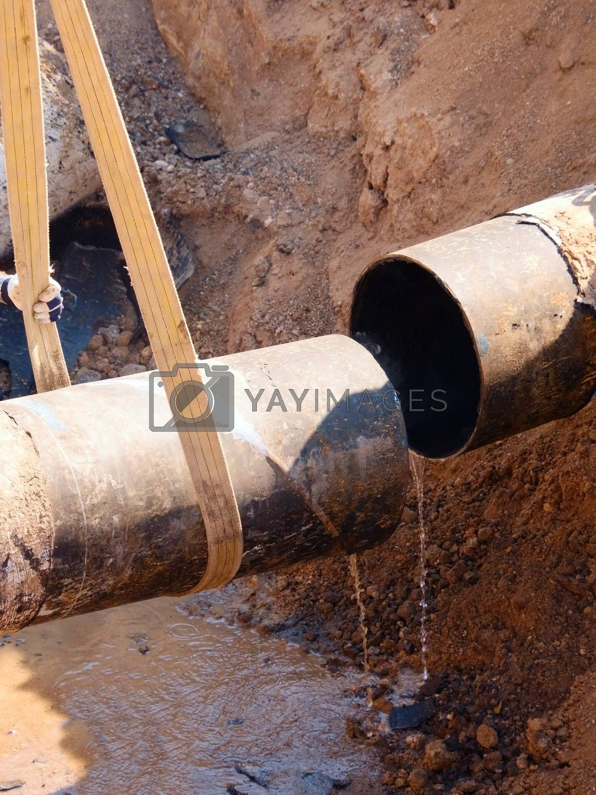 Rusty Old Iron Pipe With Clear Water Flowing From It. Waste water drain pipe in clay