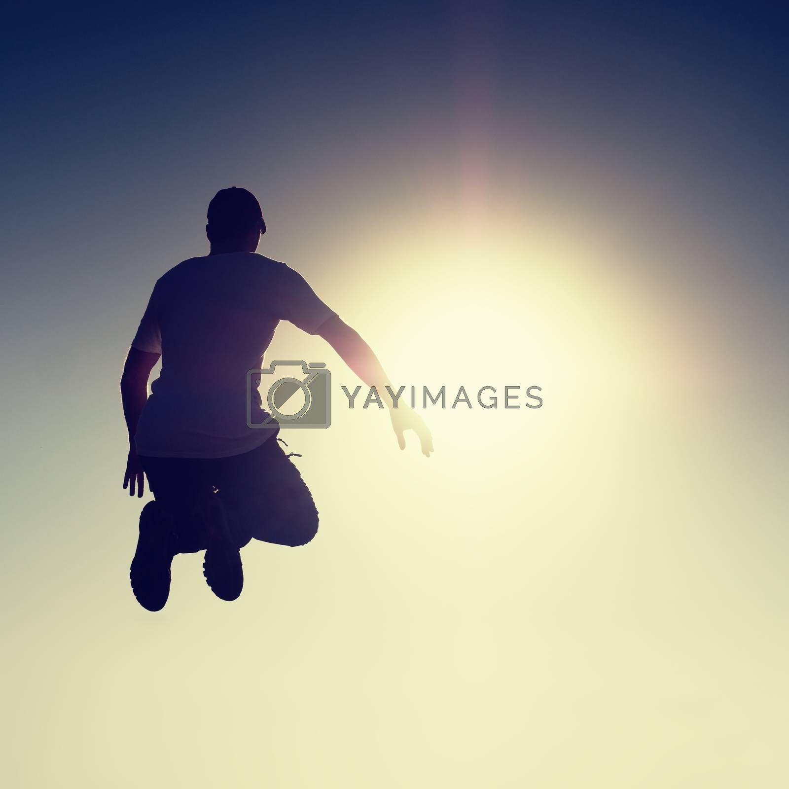Crazy man is flying over Sun on blue sky background. Silhouette of jumping man and beautiful sunset sky. Element of design. Vintage effect.
