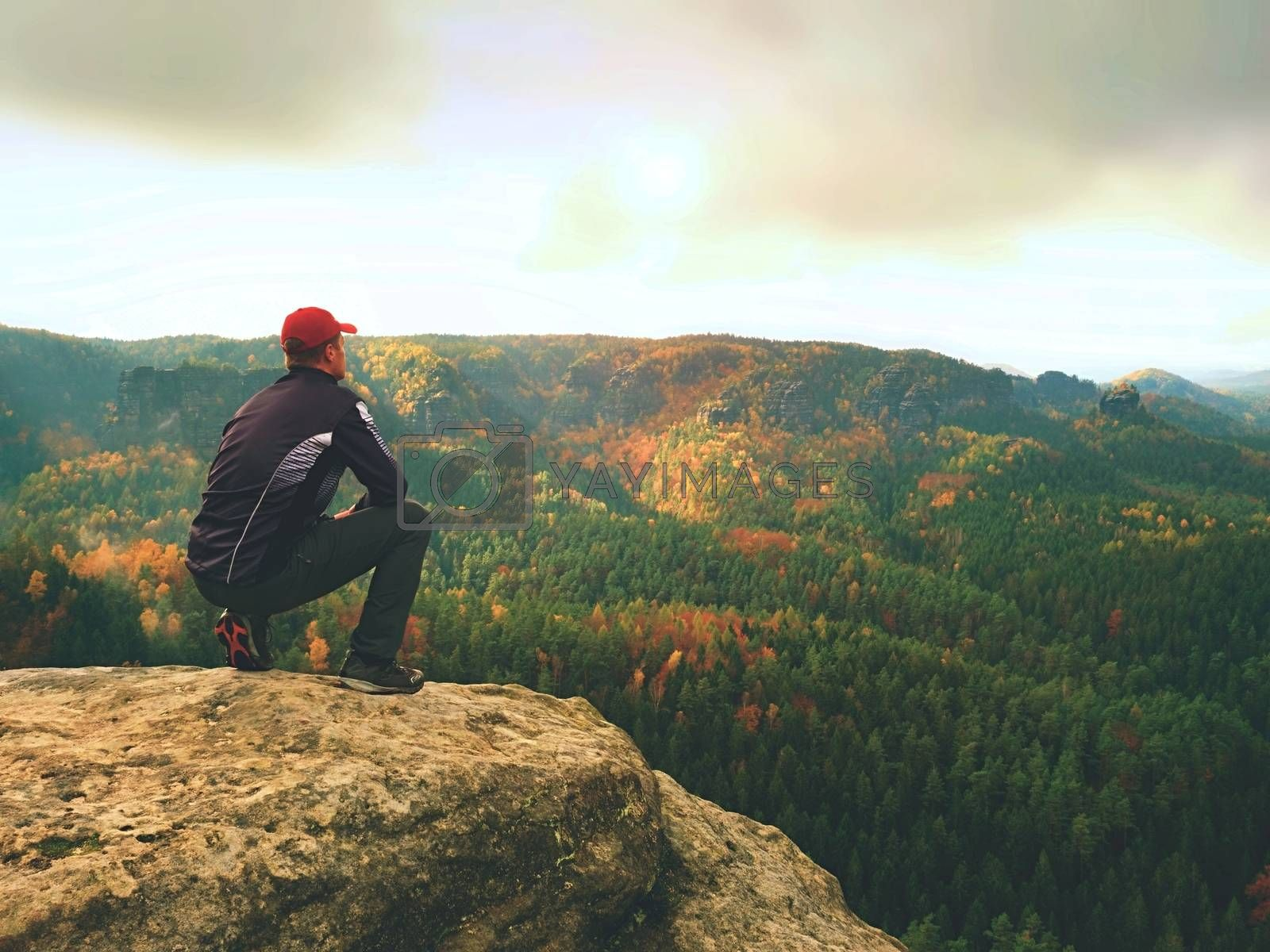Man in black outdoor clothes sit on cracked rocky empires. Fall colorfull landcape. Melancholy misty day in sandstone mountains, mist in deep valley.