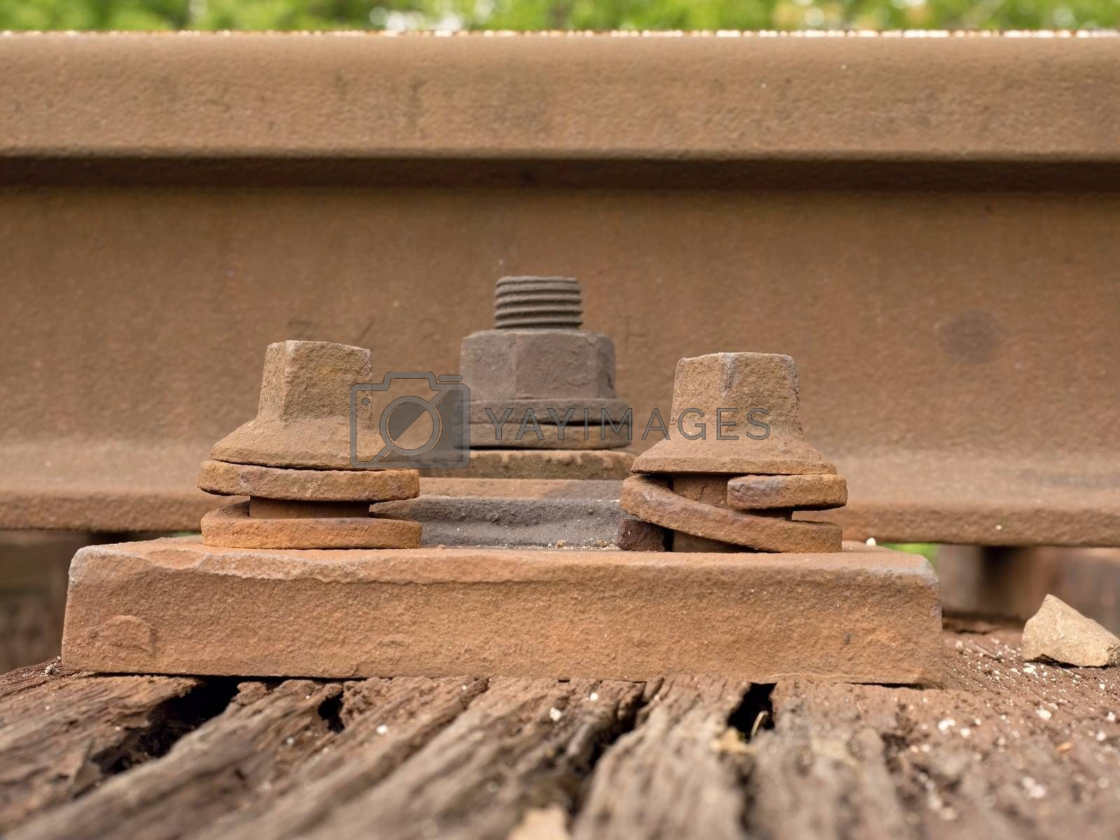 Detail of rusty screws and nut on old railroad track. Rotten wooden tie with rusty nuts and bolts. Damaged wooden railway sleeper. No train passed this railroad for a long time.