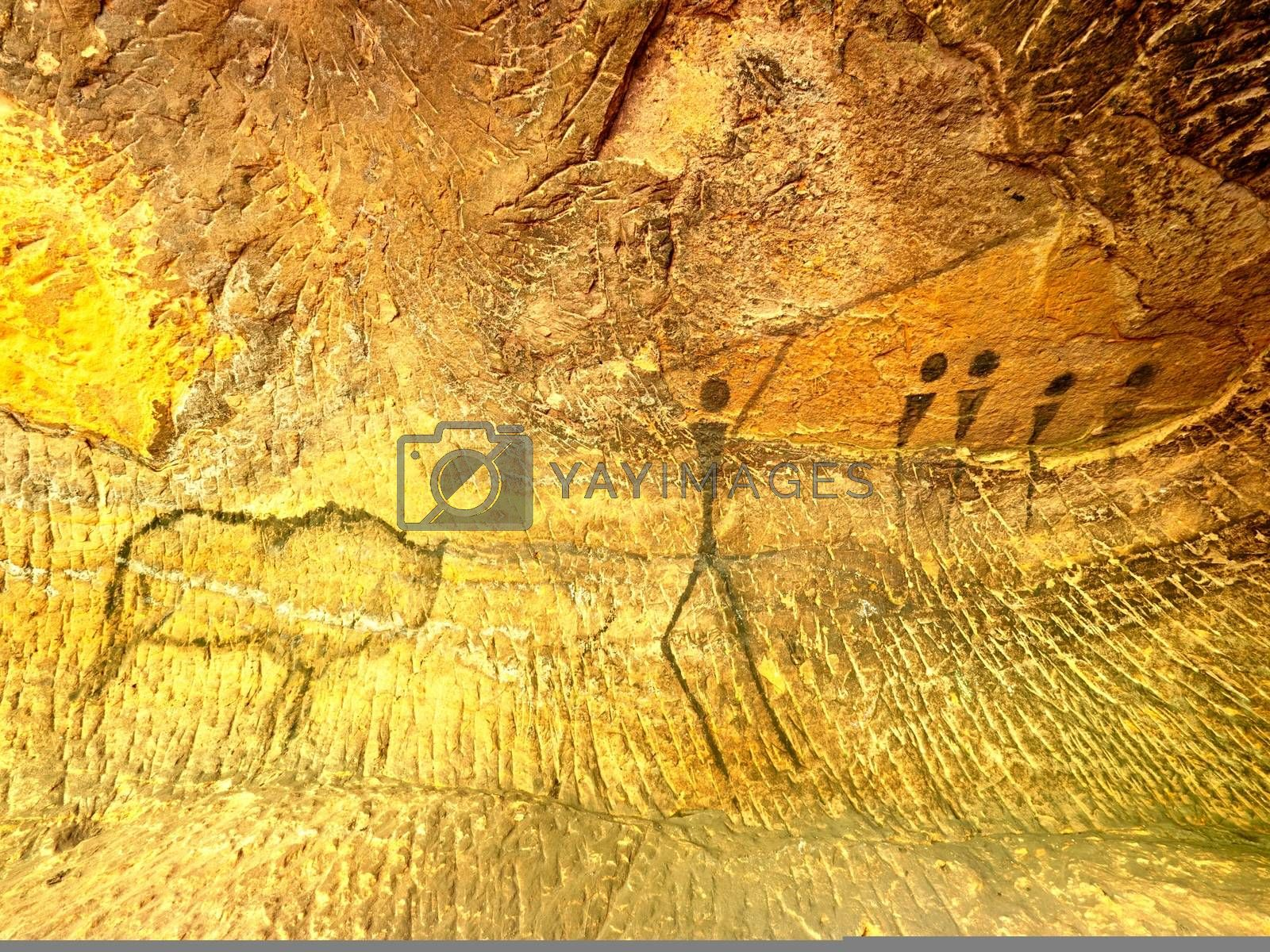 Buffalo hunting. Paint of human hunting on sandstone wall, prehistoric picture. Black carbon abstract children art in sandstone cave. Spotlight shines on caveman painting in cave
