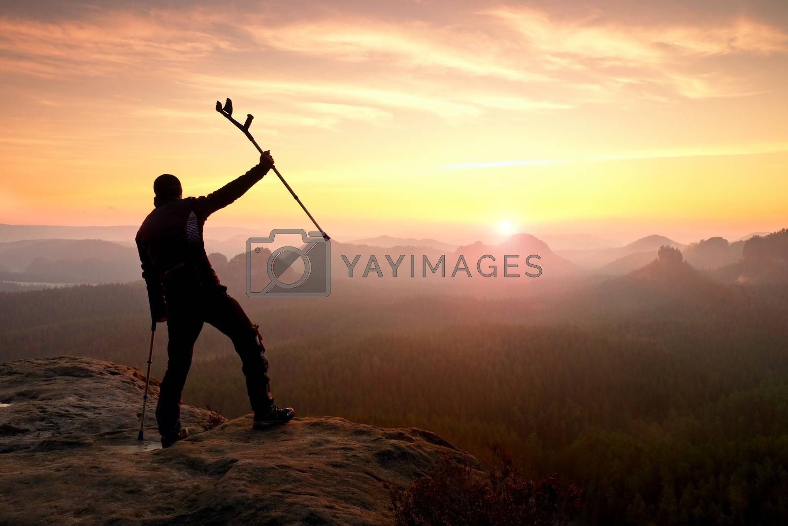 Happy man with broken leg in immobilizer and medicine pole above head stay on peak. Open misty mountain valley bellow cliff. Silhouette of tourist with hand in air. Spring daybreak