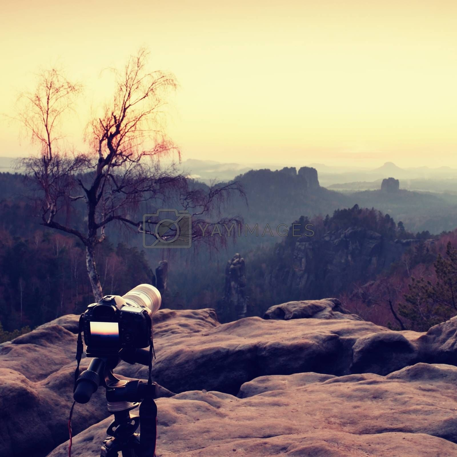 Tripod with big camera stand on mountain peak after sunset. Sharp sandstone cliffs at horizon
