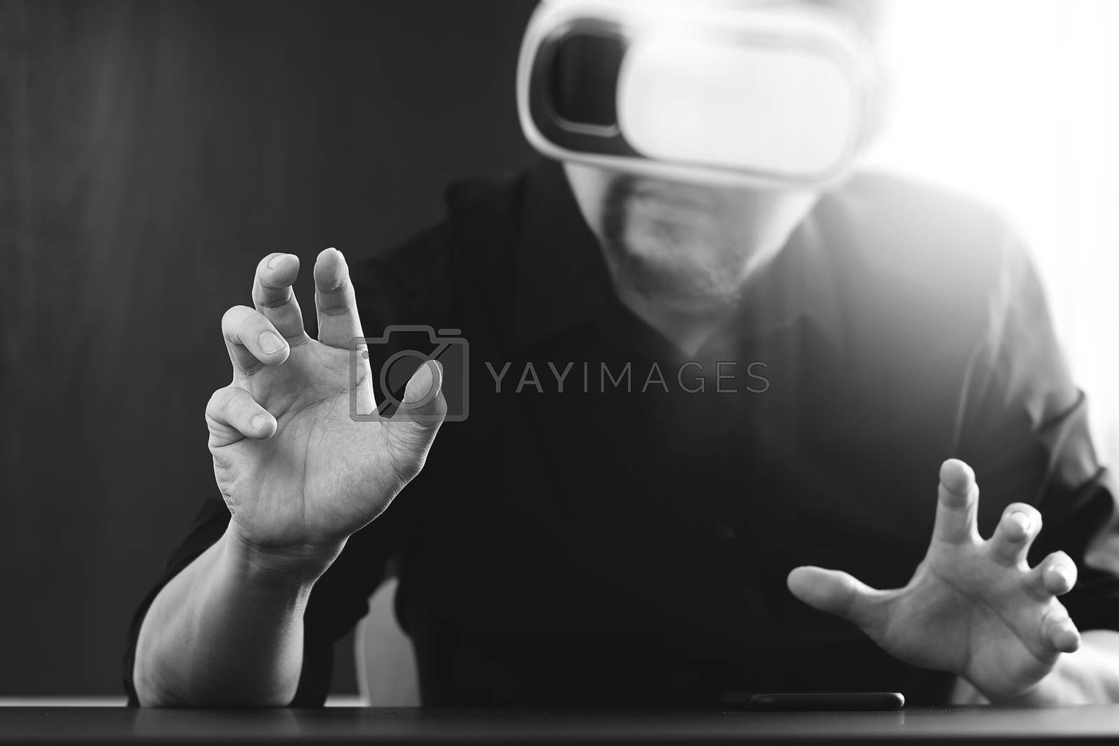 businessman wearing virtual reality goggles in modern office with mobile phone using with VR headset,black and white