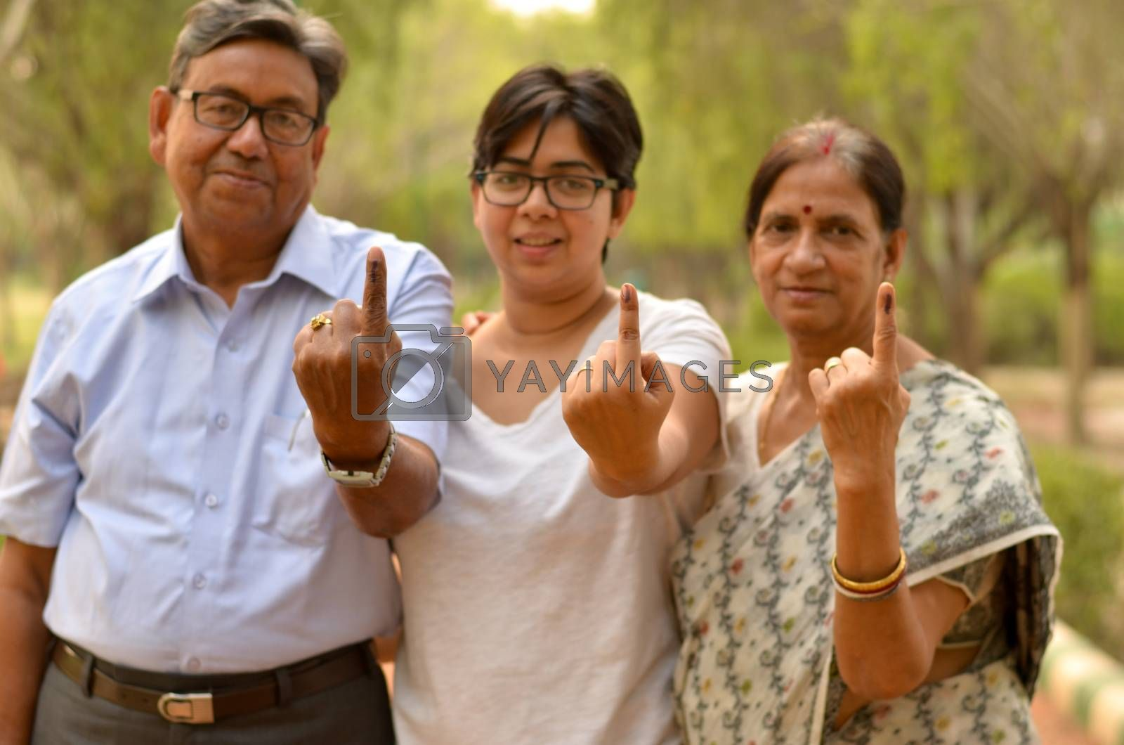 Happy Family portrait - Senior Retired parents and their daughter showing the inked finger after voting in Indian elections in an outdoor park. Celebrating world's largest democratic elections concept