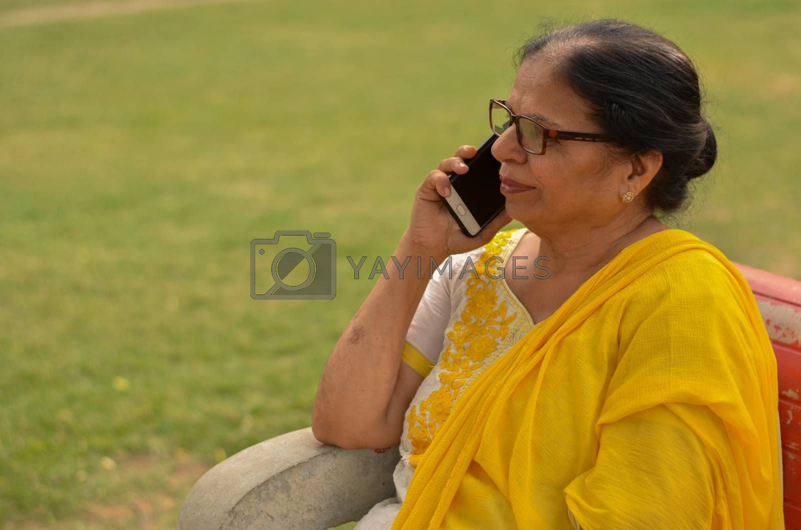Side view Senior Indian woman speaking on her smart phone, sitting on a red bench in a park in New Delhi. Concept shot showcasing technology adoption by senior citizens. Digital India