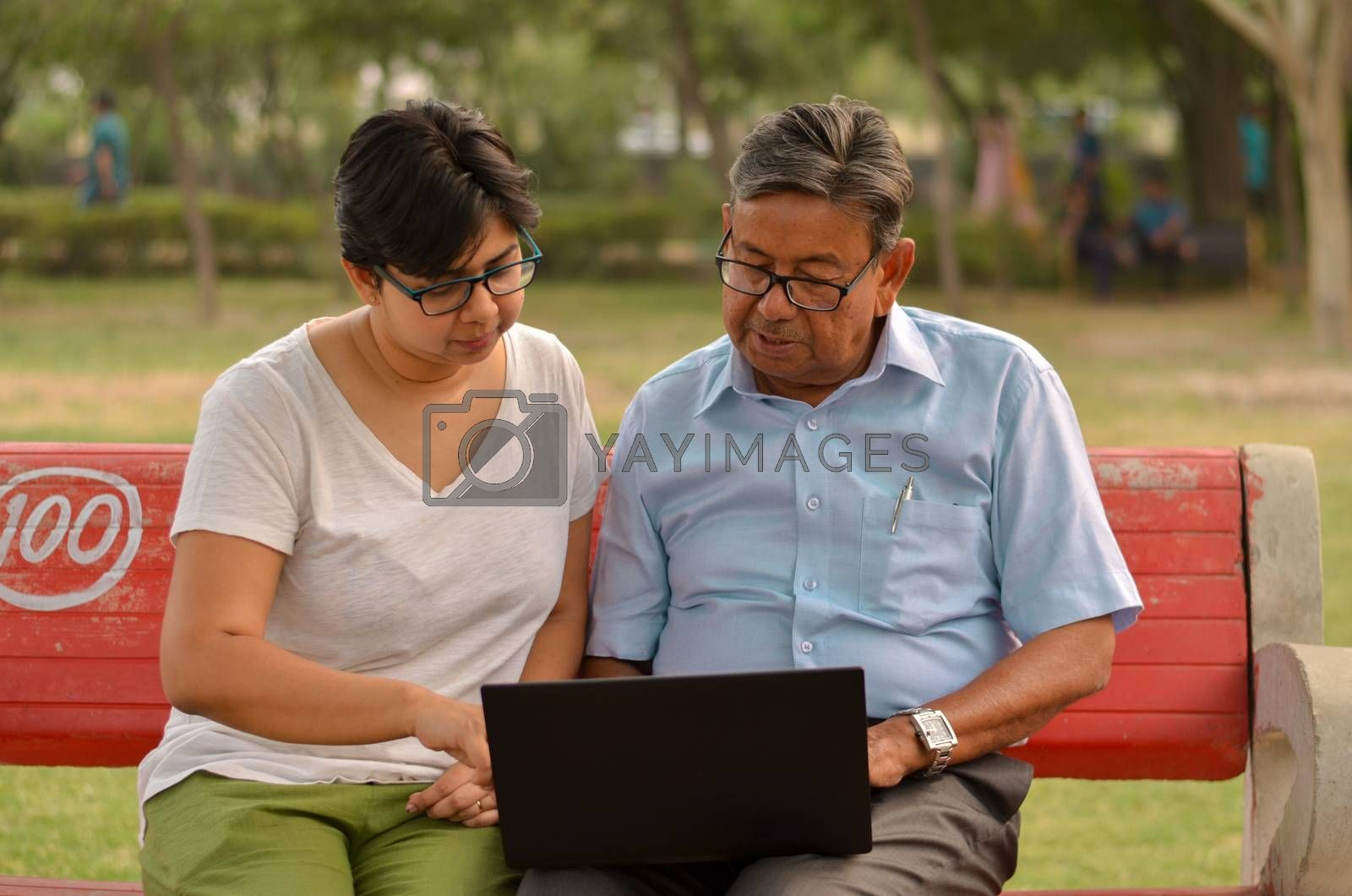 Young Indian woman manager in western formals / shirt helping old Indian man on a laptop promoting digital literacy for elderly in a park in New Delhi, India.Concept: father daughter/ Digital literacy