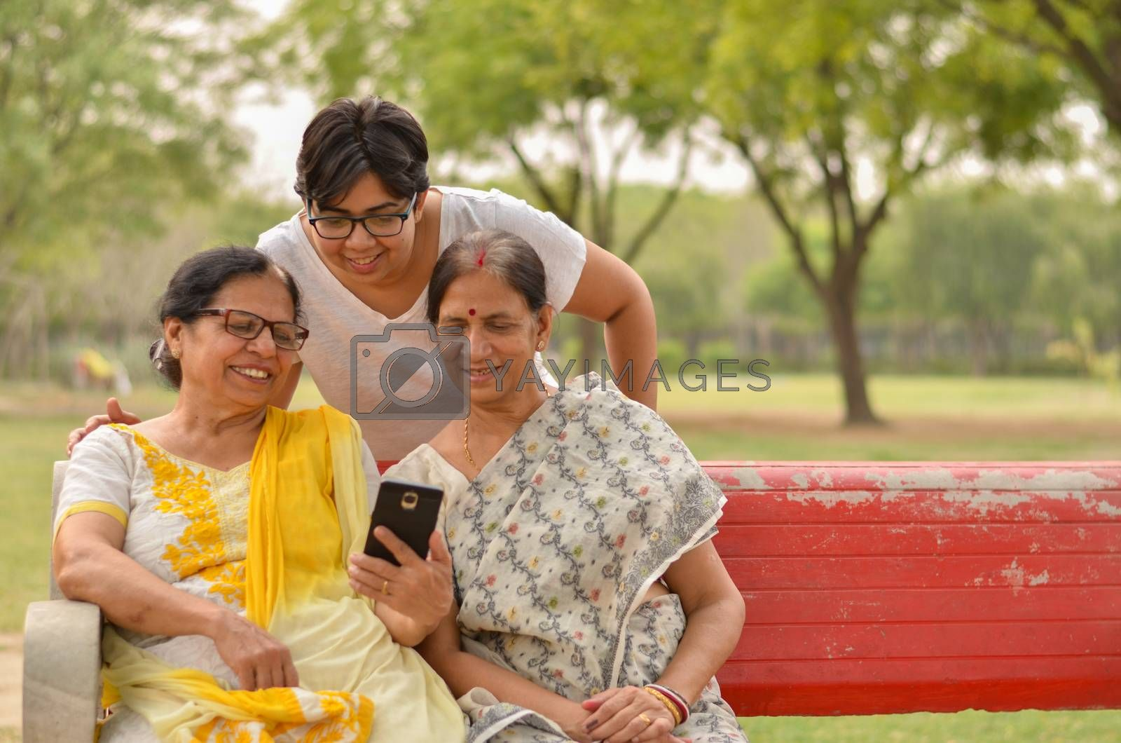 A young Indian girl with mother and mother in law - senior graceful women gossiping and smiling at the mobile phone screen while sitting on a red park bench in New Delhi, India. Concept Mother's day
