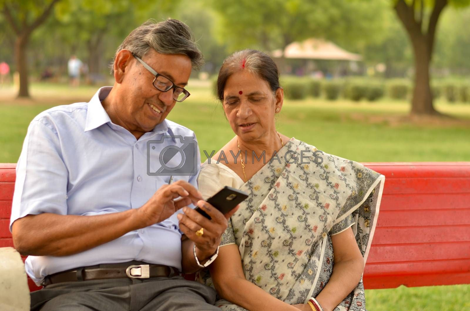 Portrait of senior couple sitting in park bench and looking at their smart phone and laughing in New Delhi, India with focus on the hands