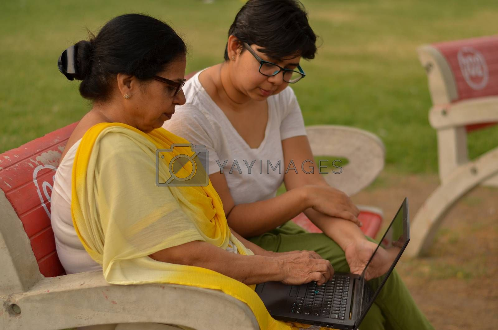Side view of young Indian girl helping an old Indian woman on a laptop sitting on a red bench in a park in New Delhi, India. Concept Digital literacy / Education