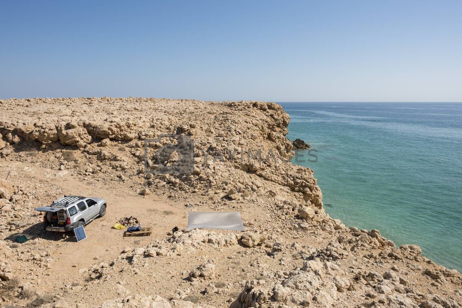 4x4 vehicle with solar panel in the wild coast of Ras Al Jinz, Sultanate of Oman. people camping in the nature with view on the ocean.