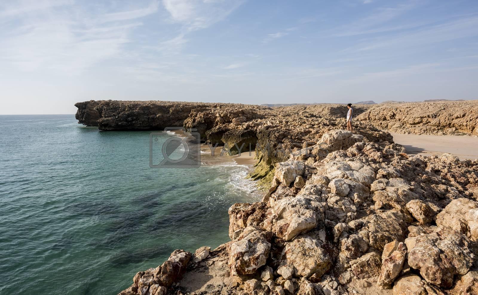 Woman admiring the wild coast of Ras Al Jinz with a sandy beach at her left, Oman