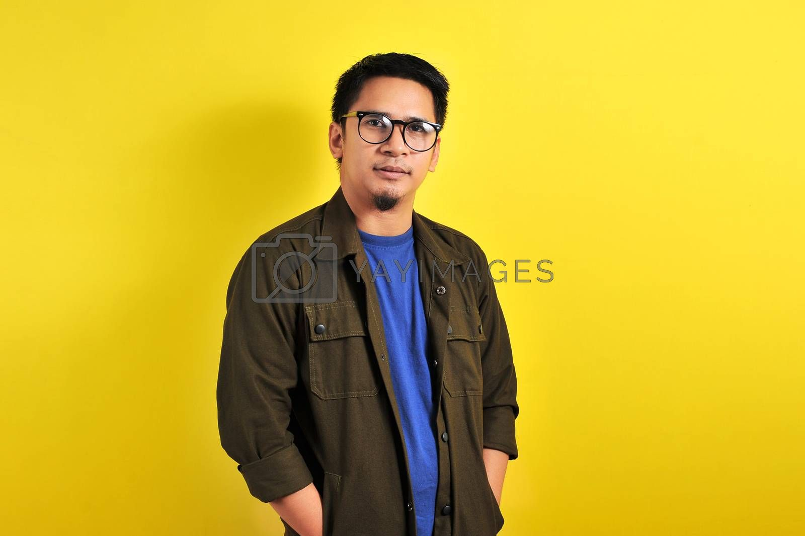 Portrait of confidence young Asian manput his hand in a jacket pocket, isolated on yellow background