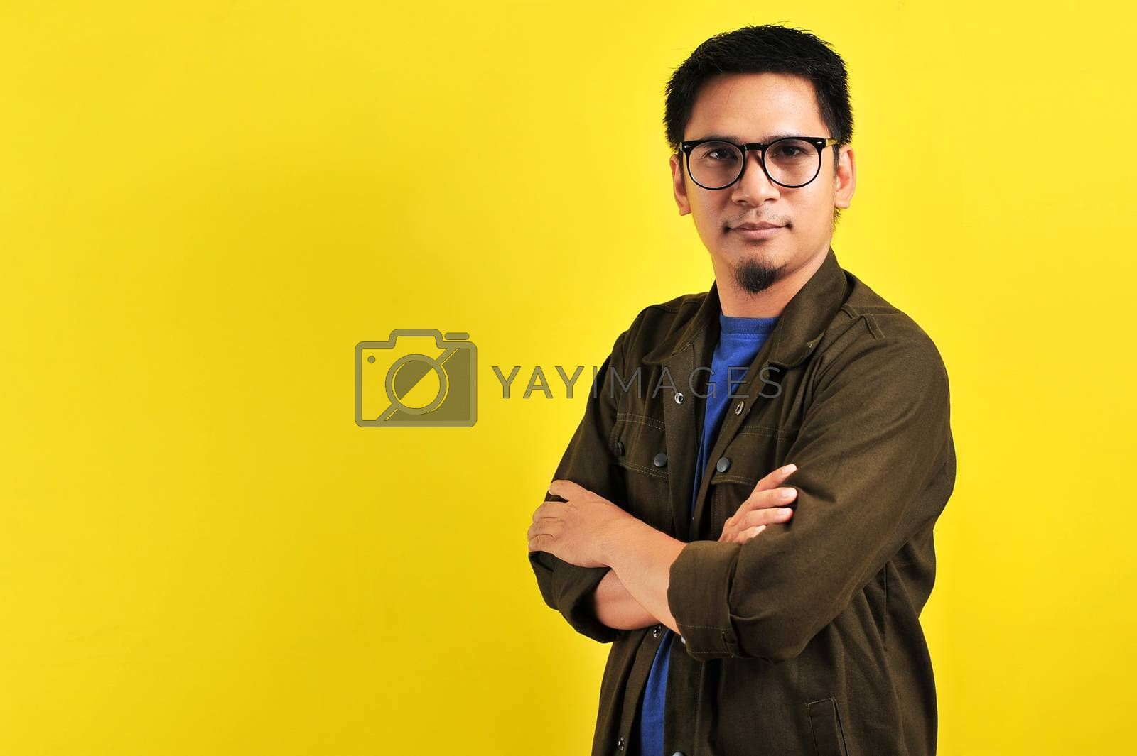 Portrait of confidence young Asian man crossed his arms, copy space, isolated on yellow background