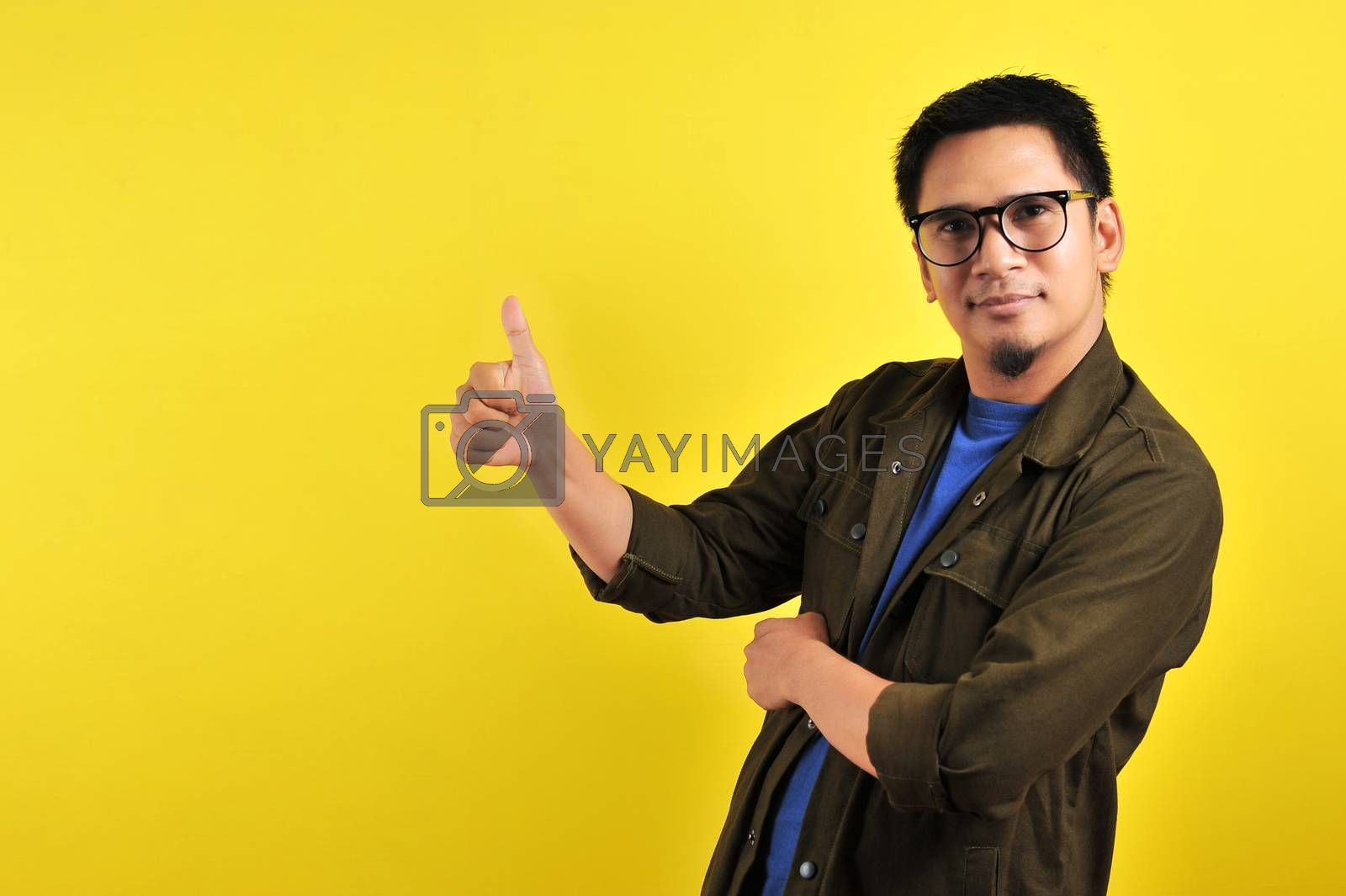 Happy of young Asian man giving thumbs up, copy space, isolated on yellow background