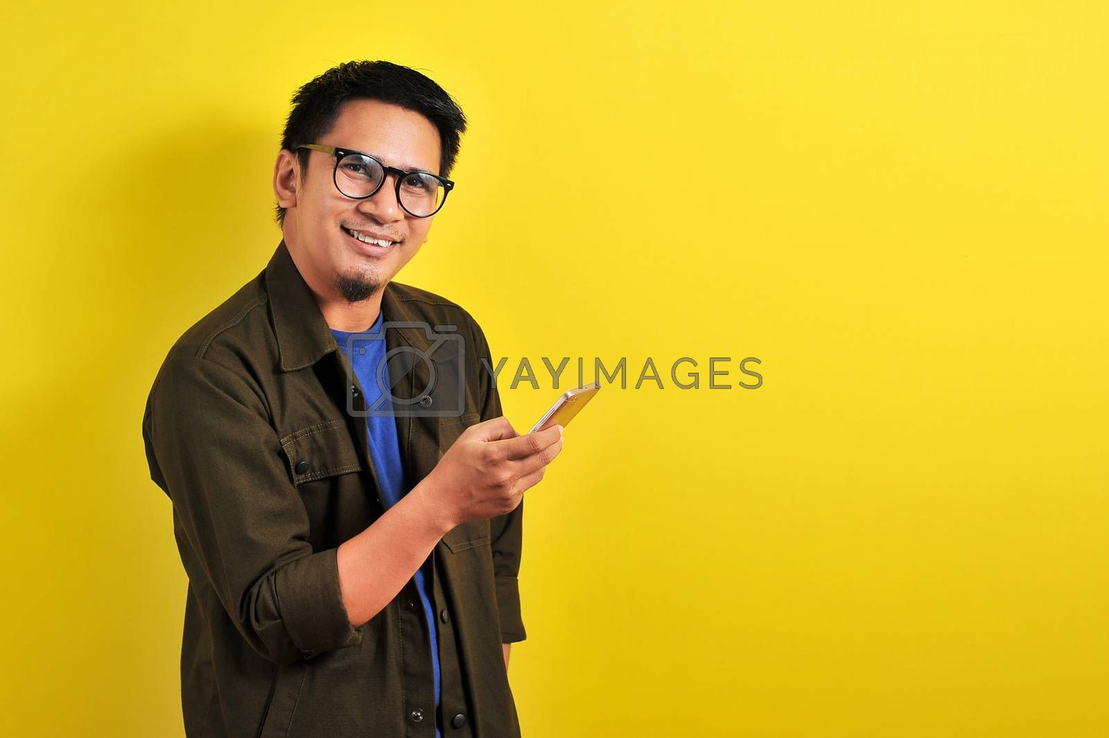 Portrait of happy smiling Asian man using smartphone wearing cas by heruan1507