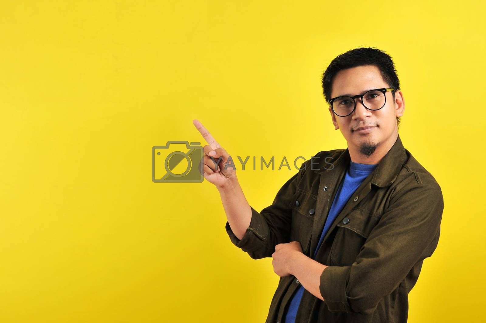Handsome of happy smiling asian man pointing of a copyspace, isolated on yellow background