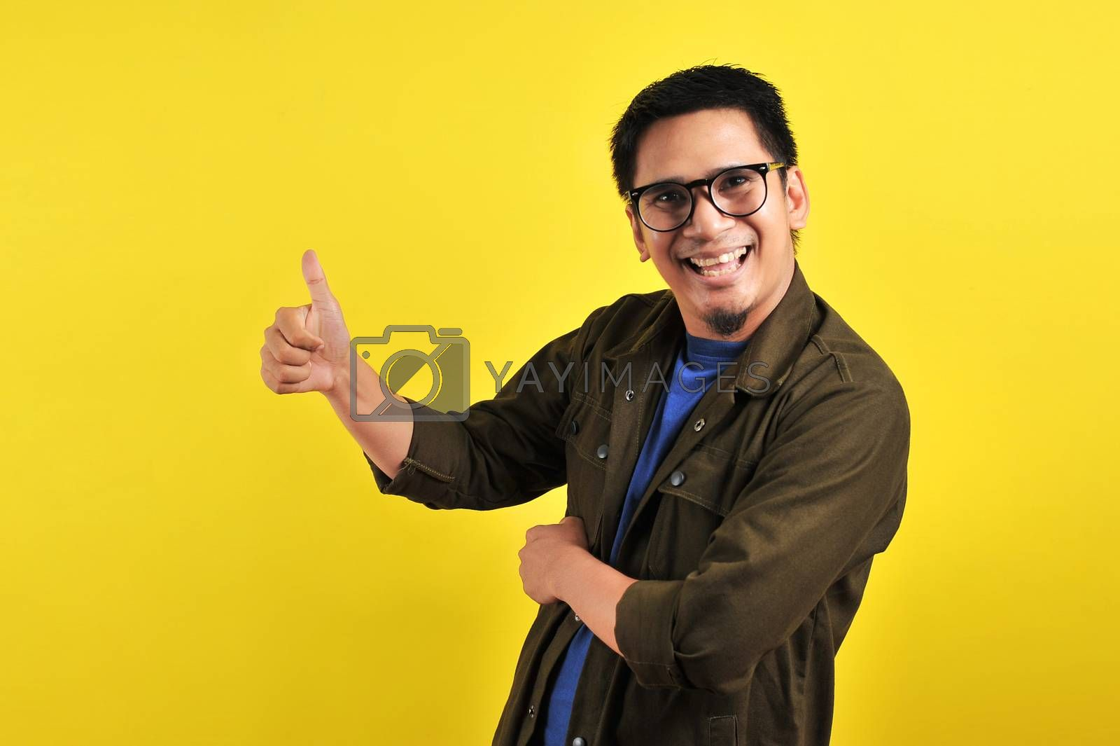 Happy of young Asian man smiling and giving thumbs up, copy space, isolated on yellow background