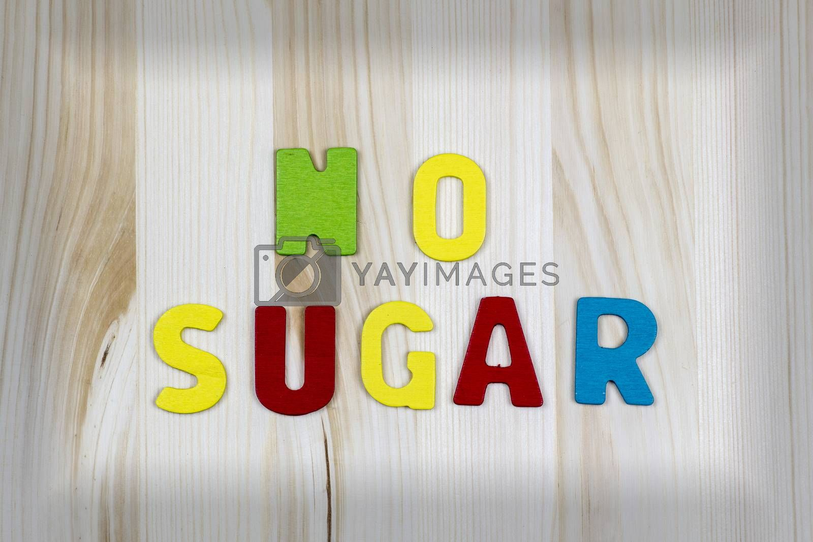 """""""NO SUGAR!"""" wriiten with colorful text wooden letters on wooden table with black border"""