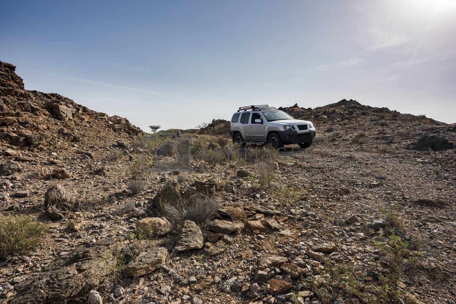 Adventure 4x4 driving rocky terrain and obstacles in arid mountains of the Sultanate of Oman, Middle East