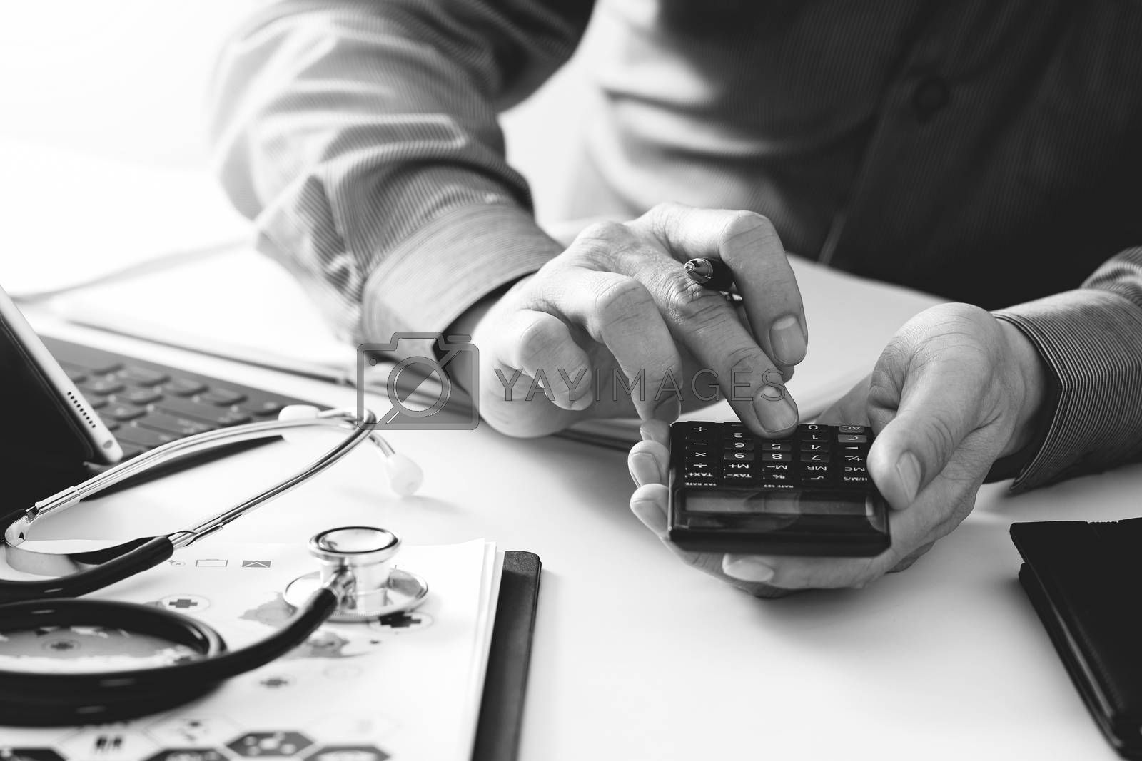 Healthcare costs and fees concept.Hand of smart doctor used a calculator for medical costs in modern hospital,black and white