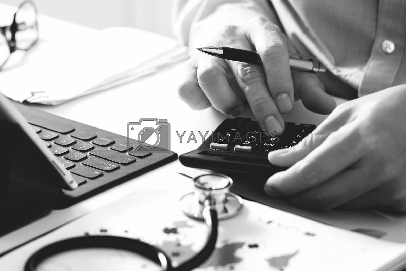 Healthcare costs and fees concept.Hand of smart doctor used a calculator for medical costs in modern hospital ,black and white