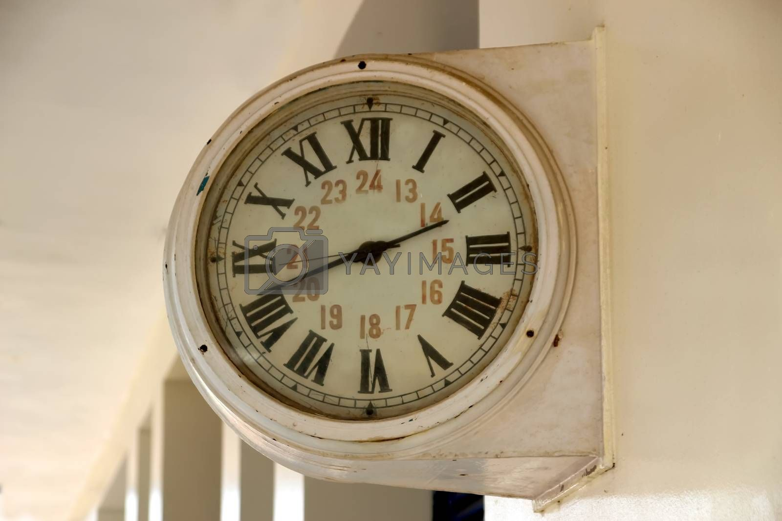 Vintage mechanical clock on the wall of the train station building, Cambodia
