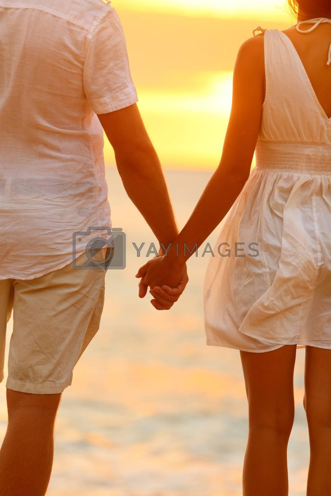 Romantic couple holding hands on beach sunset during travel. Happy woman and man in romance on honeymoon romance in beautiful sun light.